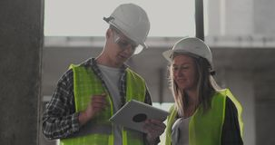 Construction worker man and architect woman in a helmet, discuss the plan of construction of house, tell each other stock video