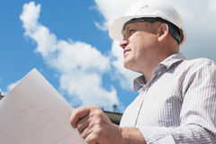 A construction worker man in white helmet holding blueprints on a background with blue sky. A construction worker man in white helmet holding in hands blueprints Royalty Free Stock Photography