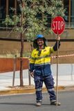 Construction worker managing traffic with stop sign, Sydney Aust. Sydney, Australia - March 25, 2017: smiling construction worker in full protective yellow and Royalty Free Stock Image