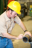 Construction Worker Marking Pipe. Construction worker marking where he wants to cut a pipe.  Authentic and accurate content depiction in accordance with industry Stock Photo