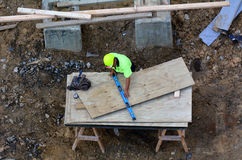 Construction worker measure piece of wood with ruler. AUCKLAND - MAR 03 2016:Construction worker.US employers often commit wage theft and violation of workplace Royalty Free Stock Image