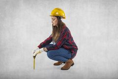 A construction worker measures something small. Symbolic Royalty Free Stock Image