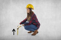 A construction worker measures something small, symbolic of Grow. Th, on the gram background Stock Photos