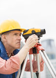 Construction Worker Measuring Distances Through Theodolite Royalty Free Stock Image