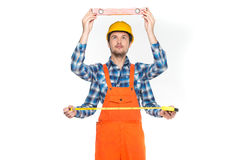 Construction worker measuring over white background. Royalty Free Stock Images