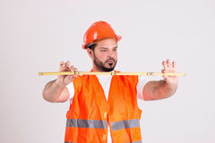 Construction Worker with Measuring Tape. Young Construction Worker in Safety Helmet and Orange Reflex Jerkin is Measuring with Measuring Tape Isolated on White Royalty Free Stock Images