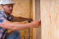 Construction Worker Measuring Width of Door Frame Royalty Free Stock Photos