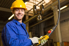 Construction worker operating crane in assembly hall Stock Photo