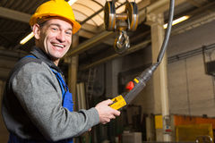 Construction worker operating crane in assembly hall Royalty Free Stock Photography