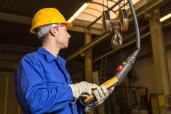Construction worker operating crane in assembly hall Stock Images