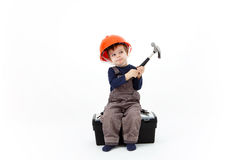 Construction worker in orange helmet with hammer sitting on tool Royalty Free Stock Images