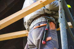 Construction worker in overalls with hammer standing on scaffold Royalty Free Stock Photos