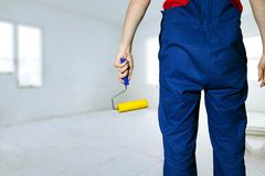 construction worker with paint roller ready for painting royalty free stock photo