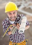 Construction Worker with paint tools in front of construction site. Digital composite of Construction Worker with paint tools in front of construction site stock photography