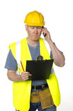 Construction worker phones and looks at clipboard Stock Photo