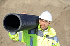Construction worker with a pipe on his shoulder Royalty Free Stock Photo