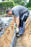Construction worker place border stones. Royalty Free Stock Photography