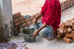Construction worker placing bricks on cement for building exteri stock photo