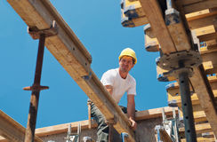 Construction worker placing formwork beams. Authentic construction worker placing slab formwork beams in construction site stock image