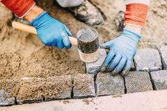 Construction worker placing stone tiles, cobblestone blocks in sand. Portrait of worker Royalty Free Stock Images
