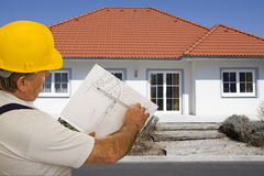 Construction worker with plan of an architect. For the planning of a house Royalty Free Stock Photo