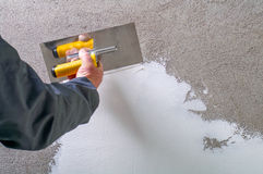 Construction worker - plastering and smoothing concrete wall wit Royalty Free Stock Photography