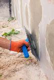 Construction worker plastering a wall and house foundation with trowel. stock images