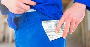 Construction Worker pocketing money notes in front of construction site stock photos