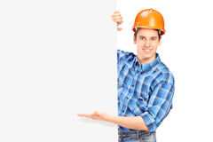 Construction worker posing behind a panel. A construction worker with helmet posing behind a blank panel isolated on white Royalty Free Stock Image