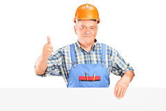 Construction worker posing behind a panel. A male construction worker holding a panel and giving thumb up isolated on white background Stock Photo
