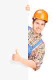 Construction worker posing and giving thumb up on a panel Royalty Free Stock Photo