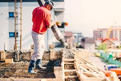 Construction worker pouring concrete in construction site, building details, industry stock image