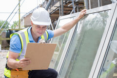 Construction Worker Preparing To Fit New Windows. Construction Worker Prepares To Fit New Windows Stock Images