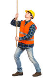 Construction worker pulling a rope. Royalty Free Stock Images