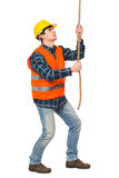 Construction worker pulling a rope. Royalty Free Stock Image