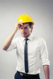 Construction worker puts on his yellow helmet. Grey background Stock Photography