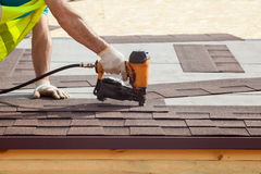 Construction worker putting the asphalt roofing shingles with nail gun on a new frame house. Construction worker putting the asphalt roofing shingles with nail stock photo