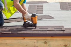 Construction worker putting the asphalt roofing shingles with nail gun on a new frame house. Stock Photos