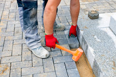 Construction worker putting concrete paving stones. Close up of a worker places paving stones in front of a private house, using a rubber hammer for fixing the Stock Photos