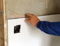 Construction worker putting white porcelain stoneware tiles in the kitchen. Bricklayer laying white tiles in reforming the kitchen of the house Stock Photos