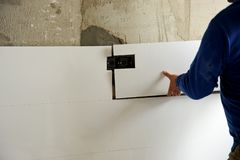 Construction worker putting white porcelain stoneware tiles in the kitchen. Bricklayer laying white tiles in reforming the kitchen of the house Stock Photography