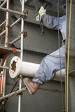 Construction Worker Ratcheting Pipe into Place Royalty Free Stock Image