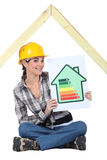 Construction worker with rating sign. Female construction worker with an energy rating sign royalty free stock photography
