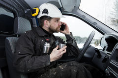 Construction worker reading papers, driving a car and talking on the phone while drinking coffee in Finland. He is wearing a white helmet and he has a dirty Stock Photos