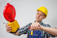 Construction worker with a red construction site-lamp Stock Photo
