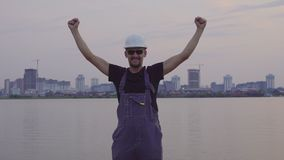 Construction worker rejoices and jumping with happy in the evening city. stock video footage