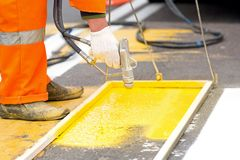 Construction worker remarking pedestrian crossing lines Royalty Free Stock Images