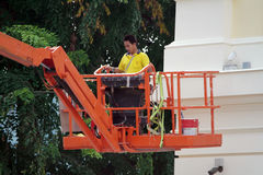 Construction Worker Renovating Building Using Skylift. Truck Stock Image