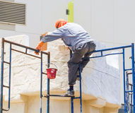 Construction worker restoring and painting outside the building. Royalty Free Stock Image