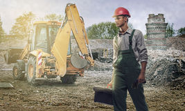 Construction worker. Road construction worker, walks determinately toward the camera. Bulldozer and residential area on the background Royalty Free Stock Images